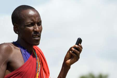 tribu: Masai Nativo con el teléfono celular en el Parque Nacional de Masai Mara, Kenia