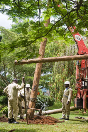 MASAKA, UGANDA - NOVEMBER 25  A unidentified team of electrician linemen work on a utility pole on November 25, 2013 in Masaka
