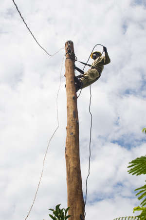 lineman: An electrician lineman working on a utility pole