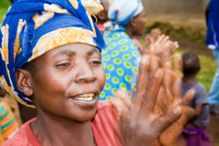 KISORO, UGANDA - DECEMBER 31, 2013  An unidentified pygmy woman claps her hands and sings  Editorial