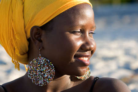 ugandan: Beautiful african woman with scarf enjoying the sun Stock Photo