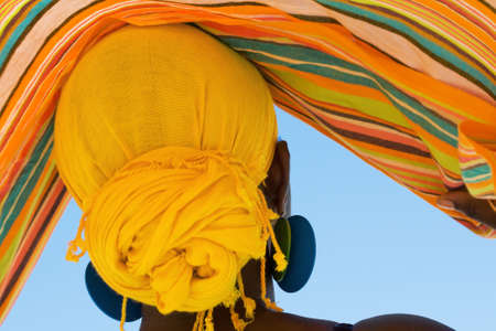 African woman with colorful head scarf from the back view