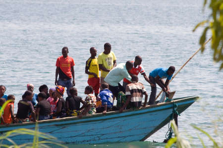 MPULUNGU, ZAMBIA - JUNE 6, 2014: Unidentified people sit in a boat, one unidentified man lifts the anchor before departure at the beach in Mpulungu on June 6, in Zambia 2014.