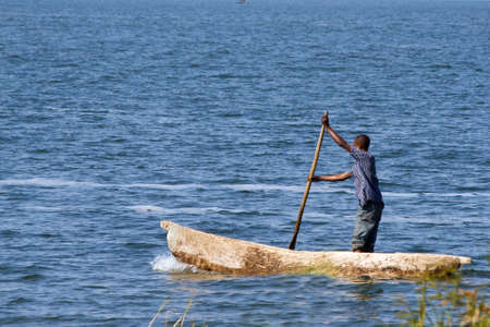 dugout: SAMFYA, ZAMBIA - JUNE 29, 2014: An unidentified man stands in the fisher boat and rows at lake Banguela. Editorial
