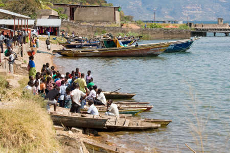 tanganyika: MPULUNGU, ZAMBIA - JUNE 6, 2014: Unidentified crowd of people sit in boats and wait for departure to their villages at fish harbor in Mpulungu on June 6, in Zambia 2014.