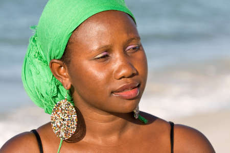 Portrait of young african woman with headscarf is looking interested  Stock Photo