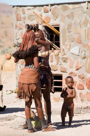 northern african: PALMWAG, NAMIBIA - NOVEMBER 14, 2014: Two unidentified women from the Himba tribe, sell souvenirs and an unidentified boy stands next to them in Palmwag, Namiba.