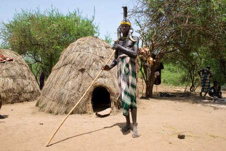identidad cultural: Valle del Omo, ETIOP�A - 13 de marzo de 2010: Un hombre no identificado de la tribu Mursi frente a una choza en su pueblo en el valle del Omo, Etiop�a. Editorial
