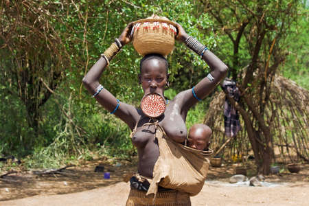 OMO VALLEY, ETHIOPIA - MARCH 13, 2010: An unidentified woman of the Mursi tribe with traditional ornaments and lip plate carries her baby on her hip and a basket on her head in front of the hut in the Omo valley, Ethiopia.