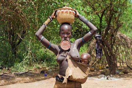 identidad cultural: Valle del Omo, ETIOPÍA - 13 de marzo de 2010: Una mujer no identificada de la tribu Mursi con adornos tradicionales y placa de labios lleva a su bebé en su cadera y una cesta en la cabeza delante de la cabaña en el valle del Omo, Etiopía.