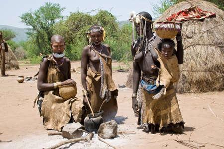 identidad cultural: Valle del Omo, ETIOPÍA - 13 de marzo de 2010: las mujeres no identificados de la tribu Mursi con adornos tradicionales y placa labio cocinar juntos en su pueblo en el valle del Omo. Una mujer no identificada lleva a su bebé en su cadera.