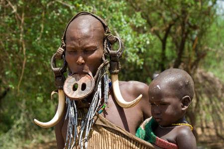 identidad cultural: Valle del Omo, ETIOPÍA - 13 de marzo de 2010: Una mujer no identificada de la tribu Mursi con adornos tradicionales y placa de labios lleva a su bebé en su pueblo en el valle del Omo, Etiopía.