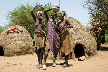 identidad cultural: Valle del Omo, ETIOP�A - 13 de marzo de 2010: las mujeres no identificados de la tribu Mursi con adornos tradicionales y placa labio cestas carry en la cabeza y dos de ellos muestran sus labios frente a las chozas de la aldea, el valle del Omo.