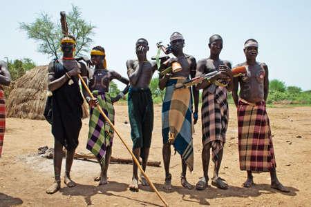 identidad cultural: Valle del Omo, ETIOPÍA - 13 de marzo de 2010: no identificados guerrero de la tribu Mursi con adornos tradicionales proteger su pueblo en el valle del Omo, Etiopía. Editorial