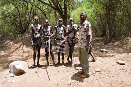 identidad cultural: Valle del Omo, ETIOPÍA - 13 de marzo de 2010: los jóvenes no identificados de la tribu Mursi en el camino a su pueblo en el valle del Omo, Etiopía. Junto a ellos un guía turístico, que es necesario para visitar el valle del Omo.