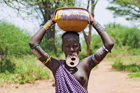 identidad cultural: Valle del Omo, ETIOPÍA - 13 de marzo de 2010: Una mujer no identificada de la tribu Mursi con adornos tradicionales y placa labio lleva una cesta en la cabeza en el valle del Omo, Etiopía.