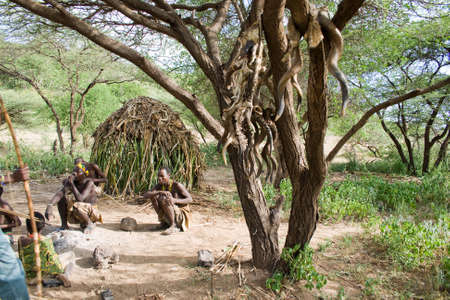 hunter gatherer: LAKE EYASI, TANZANIA - FEBRUARY 18: Unidentified Hadzabe bushmen sit next to the tree in front of a hut. At the tree there are ceremonial fetish hanging. Hadzabe tribe threatened by extinction.