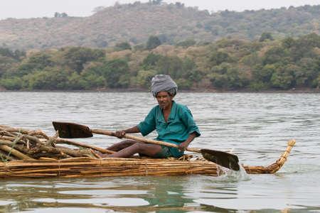 ethiopia: LAKE TANA, ETHIOPIA - FEBRUARY 26, 2010: Unidentified Ethiopian man transports logs in a papyrus boat on Lake Tana in Ethiopia. Editorial