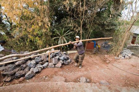 ethiopian: BARHIR DAR, ETHIOPIA - FEBRUARY 26, 2010: Unidentified Ethiopian worker carries heavy trunk to rebuild the monastery.