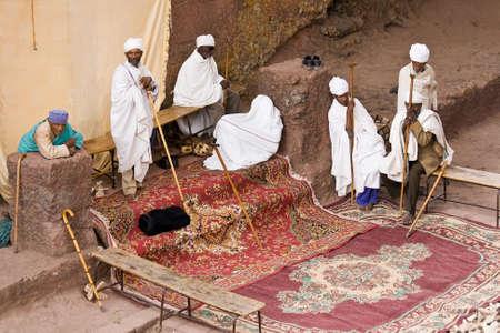 sacerdote: Lalibela, Etiop�a - 23 de febrero 2010: no identificados sacerdotes oran en una de las once iglesias excavadas en la roca monol�ticas en Lalibela