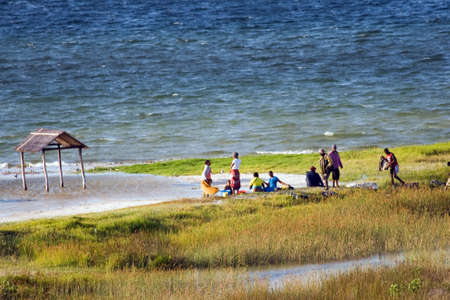 BILENE LAGOON, MOZAMBIQUE ? APRIL 08, 2015: Unidentified people sit and have a chat at the sandy beach of the Bilene lagoon.