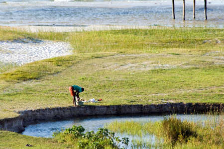 man laundry: BILENE LAGOON, MOZAMBIQUE ? APRIL 08, 2015: Unidentified man makes his laundry next to the small river. Editorial