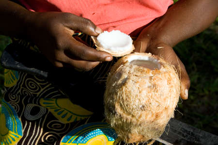 Woman shows opened coconut, which she opened with a machete. Stock Photo
