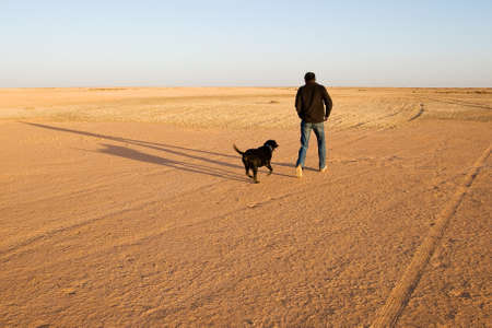 happy moment: Happy moment: Man runs and plays with his dog in the desert at sunset.