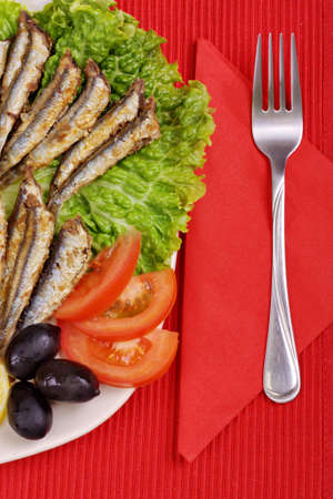 fried anchovies on lettuce leaves with lemon, tomatoes and olives photo