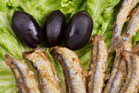 grilled fish: fried anchovies on lettuce leaves with olives Stock Photo