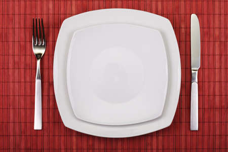 wooden table top view: white empty plate, knife and fork served on table