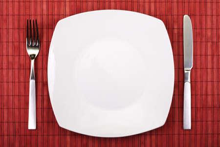 piastra acciaio: bianco piatto vuoto, coltello e forchetta servito sul tavolo