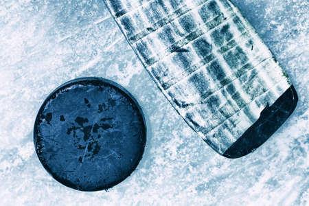 하키 스틱과 퍽입니다. 스케이트 표식으로 가득한 야외 아이스 링크의 표면. 얼음 배경입니다.