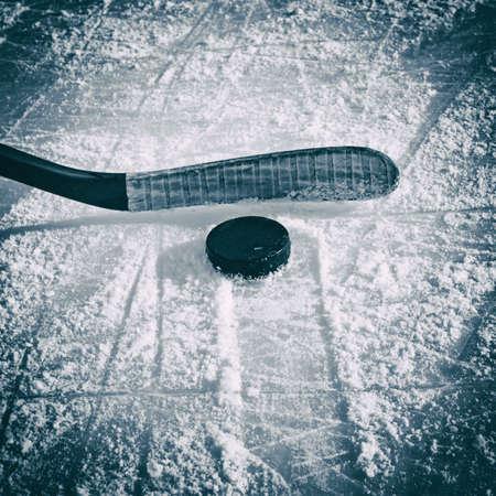 to skate: El palo de hockey y el disco sobre la pista de hielo.