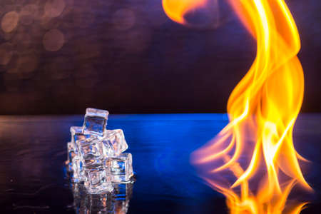 cubes of ice and fire on a water surface on an abstract background.