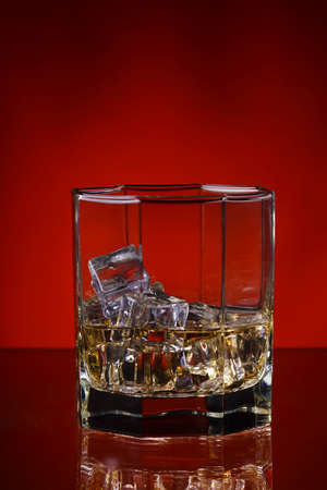 icecubes: glass of whisky with ice on a red background.