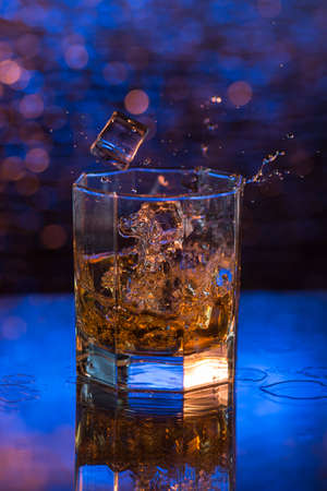 falling cubes: glass of whisky with dropped ice and splashes on a blue bokeh background.