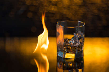 glass of whisky with ice on a black background and fire flames.