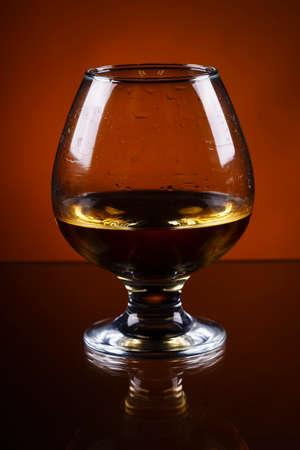 wineglass of cognac on a orange gradient background.