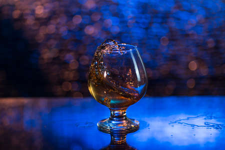 wineglass of cognac and splash on a blue bokeh background.