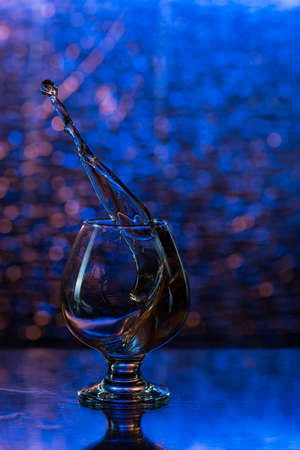 snifter: wineglass of cognac and splash on a blue bokeh background.