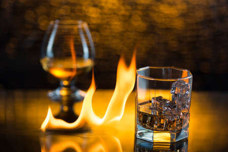 Glass o whisky with ice and wineglass of cognac and fire flames on yellow bokeh background.