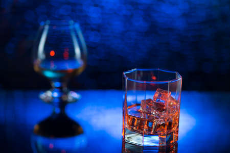 Glass o whisky with ice and wineglass of cognac on blue bokeh background.