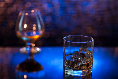 Glass o whisky with ice and wineglass of cognac on yellow-blue bokeh background.