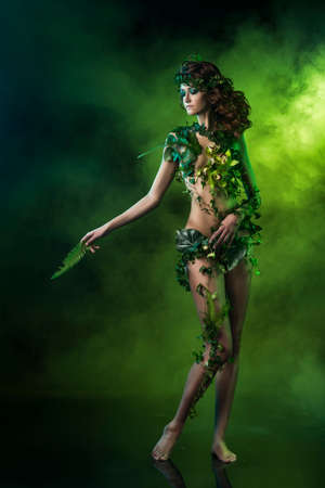 naked girl in clothes from leaves on the background of green fog.