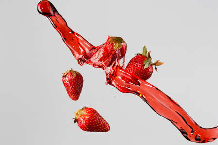 four objects: four strawberries and red juice splash isolated on a light-gray background. Stock Photo
