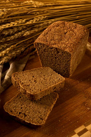 bakery products: Still life with rye bread, ears of corn on the background of wooden boards