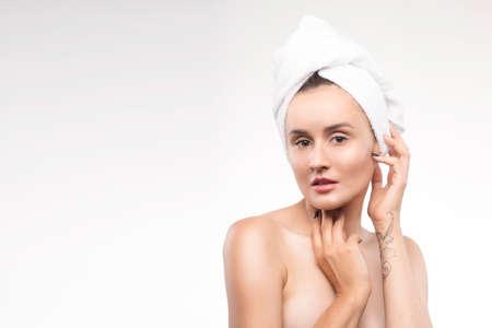 Portrait der schönen fälligen Frau mit einem weißen Tuch auf dem Kopf. Reine gesunde Haut. Spa, Kosmetik, Sauna.