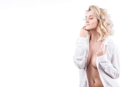 Sensual portrait of a big breasted blonde girl in an unbuttoned white mens shirt isolated on a white background. Copy space. Stock Photo