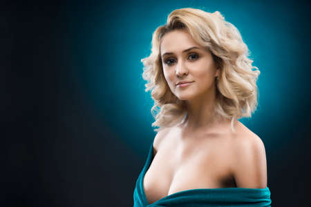 Sensual portrait of a big breasted blonde girl on a blue gradient background